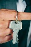 显示一个钥匙圈的衣服的人 免版税库存照片