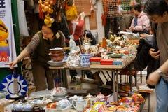 显示一些陶器和老雕象顾客的古色古香的市场贸易商 库存照片