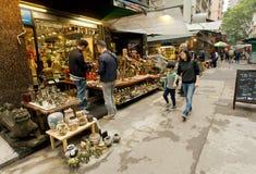 显示一些陶器和老雕象顾客的古色古香的市场贸易商 免版税图库摄影