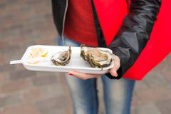 显示一只被打开的新鲜的牡蛎的妇女 库存图片