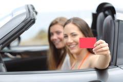 显示一张无具体金额的信用证卡片的游人在汽车 库存照片