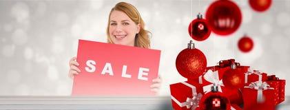 显示一张红色销售海报的逗人喜爱的金发碧眼的女人的综合图象 图库摄影