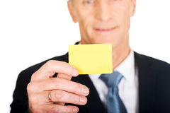 显示一张黄色身分名片的商人 免版税图库摄影