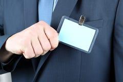 显示一枚空白的徽章的商人 免版税库存照片