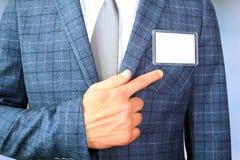 显示一枚空白的徽章的商人 免版税库存图片
