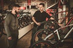 显示一辆新的自行车的推销员对感兴趣的顾客在自行车商店 免版税库存照片