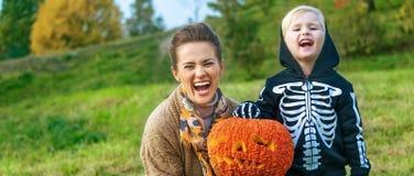 显示万圣夜南瓜杰克O'Lantern的母亲和孩子 库存照片