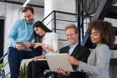 显示上司在便携式计算机上的女实业家新的战略在现代办公室,分享想法的商人队 库存照片