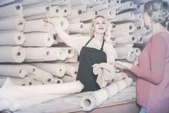 显示不同的织品的妇女卖主 免版税库存图片