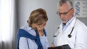显示不快乐的妇女坏考试成绩,癌症治疗,肿瘤学的医生 免版税库存照片