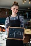 显示与开放标志的女服务员画象板岩 免版税库存照片
