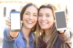 显示两个巧妙的电话屏幕的朋友 免版税库存照片