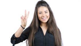 显示两个手指或胜利姿态, isol的愉快的微笑的美丽的少妇 库存图片