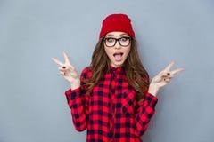 显示两个手指标志的快乐的妇女 免版税库存图片