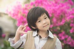 显示中指的逗人喜爱的亚裔孩子在公园 库存图片