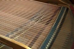 显示串、钉和共鸣板的大平台钢琴特写镜头 库存照片