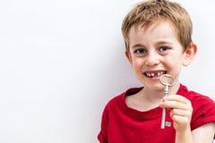 显示乐趣齿妖的微笑的无牙的男孩一把钥匙 免版税图库摄影