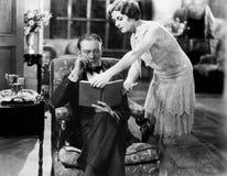 显示书的一个少妇的档案对坐一个的人在扶手椅子(所有人被描述不是更长生存和没有庄园 免版税库存图片
