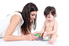 显示书的可爱的母亲对她的女儿 免版税库存图片