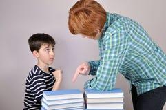 显示书的妇女对一个年轻男孩 免版税库存图片