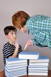 显示书的妇女对一个年轻男孩 库存图片