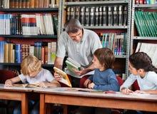 显示书的成熟老师对男小学生  库存图片