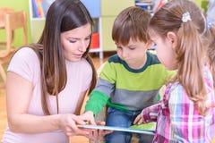 显示书的老师对孩子在Nurcery 库存图片