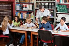 显示书的老师对男小学生在图书馆 图库摄影