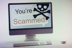 显示互联网欺骗和诈欺警告在屏幕上的计算机 免版税库存照片