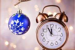 显示五分钟的葡萄酒铜闹钟对午夜 读秒新年度 与装饰品垂悬的蓝色圣诞树球 免版税库存图片