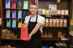 显示产品的男性推销员画象在咖啡商店 库存照片