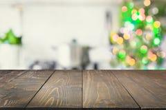 显示产品的空的木桌面和有圣诞树的被弄脏的厨房作为背景 库存图片