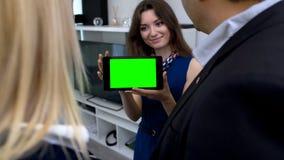 显示他们片剂的新的家的夫妇计划微笑的女孩有绿色屏幕的 免版税库存图片