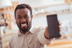显示他新的电话的快乐的人在咖啡馆 库存图片