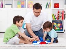 显示他的儿子一个新的玩具的父亲 库存照片