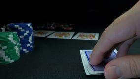 显示他的甲板的人在扑克牌游戏 纸牌运动员在背景中登记他的手,两一点,芯片在绿色 免版税库存照片