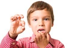 显示他的第一颗失去的牛奶牙的年轻男孩 免版税库存照片
