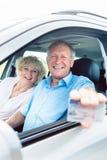 显示他的驾照的一名愉快的老人的画象 图库摄影