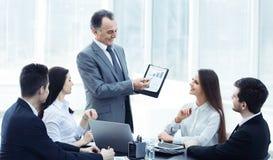 显示企业队,与财务数据的一张图表的微笑的经理 库存照片