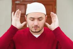 显示伊斯兰教的祷告的年轻回教人 免版税库存照片