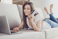 显示信用卡和在网上做互联网的愉快的少妇 库存照片
