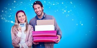 显示信用卡和运载箱子的微笑的夫妇的综合图象 免版税库存图片