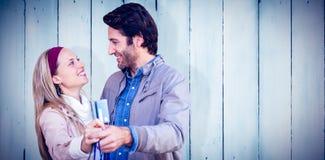 显示信用卡和购物袋的微笑的夫妇的综合图象 免版税库存照片