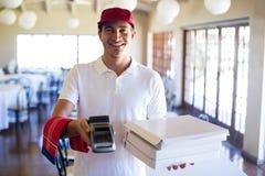 显示信用卡机器的愉快的薄饼送货人 免版税库存照片
