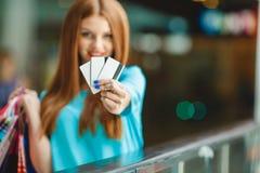 显示信用卡的俏丽的夫人在购物中心 免版税库存图片