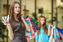 显示信用卡的俏丽的夫人在购物中心 免版税库存照片