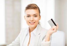 显示信用卡的微笑的女实业家 免版税库存图片