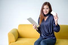 显示信用卡的美丽的亚裔年轻女人拿着在网上购物数字片剂的计算机 哇 微笑的激动的女孩与 免版税库存图片