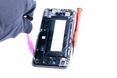 显示修理的照片有螺丝刀的一个残破的手机的过程在流动设备修理的实验室  免版税库存照片