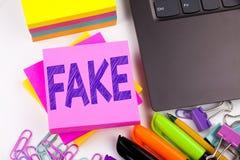 显示假新闻价值的文字文本有在有周围的办公室例如膝上型计算机,标志,笔 假新闻的Wo企业概念 库存图片